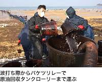 波打ち際からバケツリレーで原油回収タンクローリーまで運ぶ