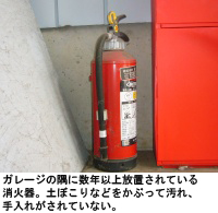 ガレージの隅に数年以上放置されている消火器。土ぼこりなどをかぶって汚れ、手入れがされていない。